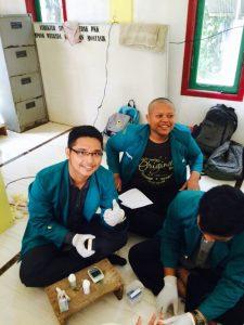 Mahasiswa bersama masyarakat sedang melakukan kegiatan pemeriksaan kesehatan