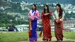 "TO GO WITH Bhutan-politics-economy-health-labour-social-youth,FEATURE by Rachel O'BRIEN Schoolgirls wear traditional Bhutanese dresses before a cultural event to celebrate the birth date of Bhutan's fourth king at a local school in Thimphu on June 2, 2013.   It is known as ""the last Shangri-La"" -- a remote Himalayan nation, rich in natural beauty and Buddhist culture, where national happiness is prioritised over economic growth. But urban youngsters in the kingdom of Bhutan are quick to challenge its rosy reputation.  AFP PHOTO/ROBERTO SCHMIDT        (Photo credit should read ROBERTO SCHMIDT/AFP/Getty Images)"